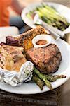 Steak de bœuf grillé avec pommes de terre au four, maïs en épi, asperges