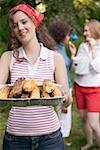 Junge Frau mit gegrillter Mais Maiskolben zu einem barbecue