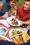 Couple avec côtes levées grillées, maïs en épi, salade, sur l'herbe