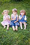 Three children with ice cream cones sitting on grass