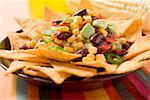 Nachos avec haricots, maïs doux, anneaux avocat et piment