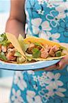Femme tenant la plaque avec deux tacos