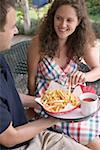 Couple assis sur la terrasse à manger des chips