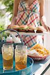 Eistee, Tee und Chips am Tisch, Frau Hamburger servieren