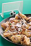 Kaiserschmarren (Emperor's pancake) in pan with toy footballers