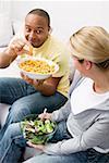 Couple sur le canapé avec des bouffées d'arachide et salade