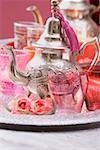 Silberne Teekanne, Gläser, Rosen und Windlichter auf Tablett
