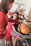 Femme mettant la Turquie sur la cuisinière, fille en arrière-plan