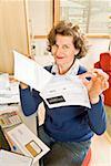 Frau hält Rechnungen im home-office