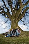 Teenage friends sitting underneath tree