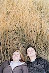 Teenage couple sleeping in grassy field