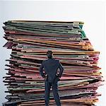 Vue arrière d'un homme d'affaires devant une pile de livres