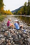 Femmes relaxantes par la rivière Methow après l'exercice, la vallée de Methow, près de Mazama, Washington, États-Unis