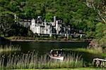 Kylemore Abbey, Connemara, County Galway, Irland; Menschen im Boot vor der historischen Abtei