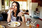 Woman Eating Breakfast in Restaurant