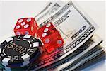 Zwei Würfel mit einem Glücksspiel-Chip auf einem Stapel von US-Dollar-Scheine