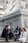 Vier Unternehmer und eine geschäftsfrau auf Treppe sitzen und diskutieren