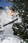Skieur sautant à travers les arbres