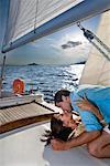 Couple pose sur voilier, baiser