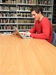 Jeune homme travaillant à l'ordinateur dans la bibliothèque