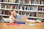 Ennuyé de jeune femme en bibliothèque