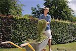 Man putting cut grass in wheelbarrow