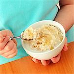 Girl eating porridge with honey