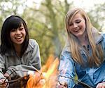Deux adolescentes rôtir des guimauves sur un feu de camp le sourire