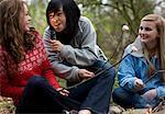Groupe d'adolescentes torréfaction guimauves sur un feu de camp est souriant et briller une lampe de poche sur son visage