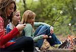 Groupe d'adolescentes torréfaction guimauves sur un feu de camp est à l'aide d'un téléphone cellulaire