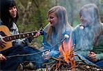 Groupe d'adolescentes torréfaction guimauves sur un feu de camp est jouer de la guitare