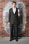 Homme d'affaires avec le pinceau de peinture de mur de brique