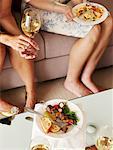 Femme sur le canapé avec vin et dîner