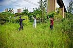 Police Officer Arresting Two Men in a Grassy Field