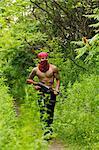 Homme marche sur la piste forestière, transportant des armes à feu