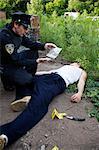 Polizist und Rettungssanitäter mit Leiche am Tatort, Toronto, Ontario, Kanada