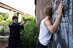 Policier pointant un pistolet à l'homme contre le mur, Toronto, Ontario, Canada