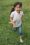 Smiling girl running in park