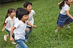 Kinder, die zusammen im Park laufen