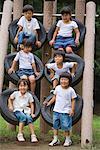 Lächelnde Kinder sitzen auf Reifen Klettern Frame im park