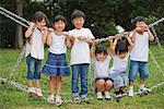 Lächelnde Kinder stehend auf Klettergerüst