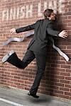 Homme d'affaires en cours d'exécution à la ligne d'arrivée à mur