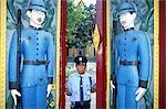 Thailand, Bangkok, Wat Rajobopit Buddist temple, warden opening the carved gates