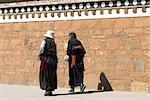China, Gansu, Gannan, Hézuo, women by the wall of Serkhar Guthog Tibetan Buddhist monastery