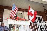 Couple senior sur le porche de l'avant avec des drapeaux américains et canadiens