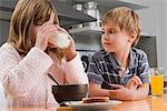 Girl having breakfast beside her brother