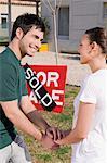 Junges Paar Hand in Hand der jeweils anderen vor eine Informationstafel verkauft