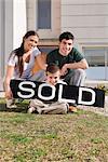 Junges Paar und ihr Sohn sitzt mit einer Informationstafel verkauft