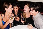 Deux jeunes couples assis à une table et de profiter de cocktails