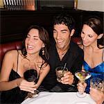 Trois amis assis à une table et souriant